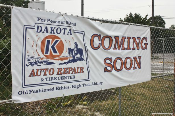 Dakota Auto Repair Arlington Heights. Announcing a new location and fence mounted outside the construction site.