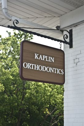 Kaplin Orthodontics Arlington Heights.  Sandblasted wooden sign with painted letters and outline.  Hanging your sign saves space and directs customers from a different angle.