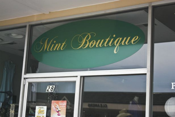Mint Boutique Arlington Heights.  Green oval backing with cursive gold lettering.