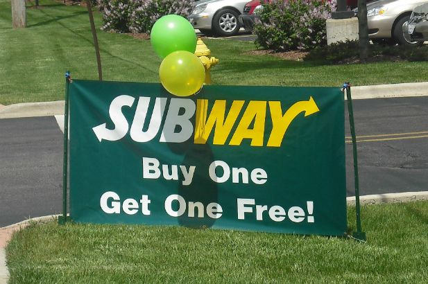 "A commonly requested ""buy 1 get 1"" doublesided banner with brass grommets for mounting."
