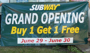 "Grand opening banner featuring a ""by 1 get 1"" deal."
